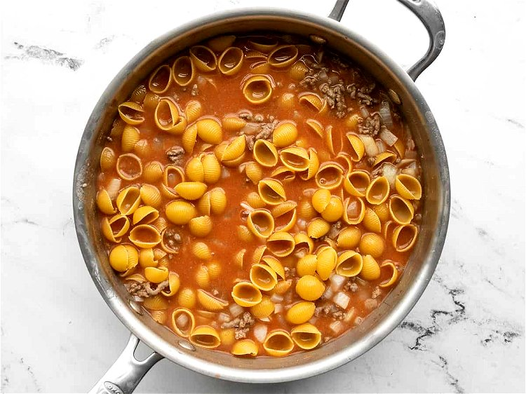 Image of Add the uncooked pasta to the skillet and stir to...