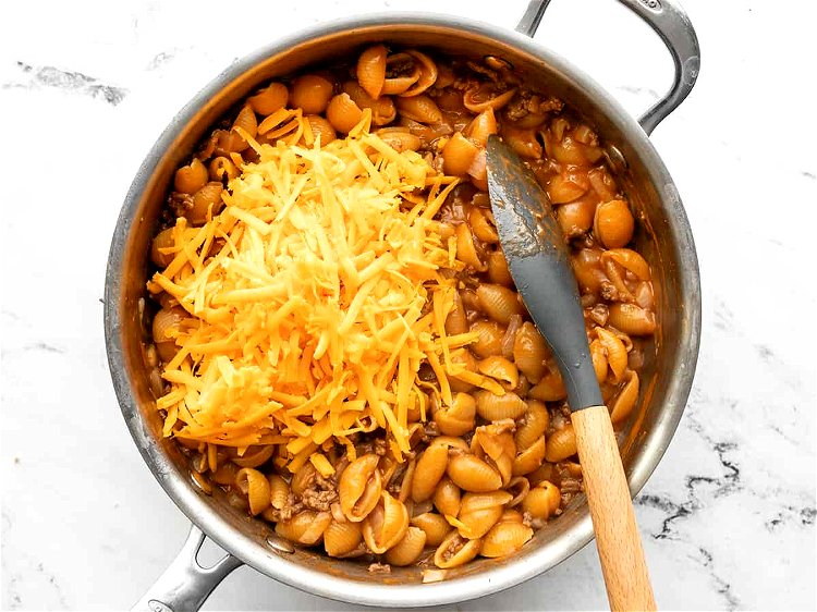 Image of Add the shredded cheddar to the skillet and stir until...